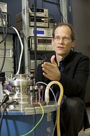 Le professeur Taillefer examine le cryostat qui sert à recevoir le réfrigérateur à dilution dans lequel seront mesurées les propriétés électroniques de matériaux supraconducteurs à des températures de quelques millièmes de degrés au-dessus du zéro absolu et sous des champs magnétiques 300000 fois plus élevés que le champ magnétique terrestre.