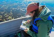 Une des étudiantes impliquées dans la Clinique en pleine action. Marie Durand identifie les différentes plantes aquatiques en vue de vérifier s'il s'agit de plantes envahissantes.