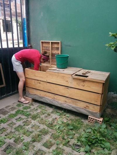 Voici le bac de compost construit lors du volet 1. Les stagiaires de l'équipe actuelle l'utilisent tous les jours pour y mettre les restes de table. Aujourd'hui, il y a déjà deux compartiments remplis de matières compostables.