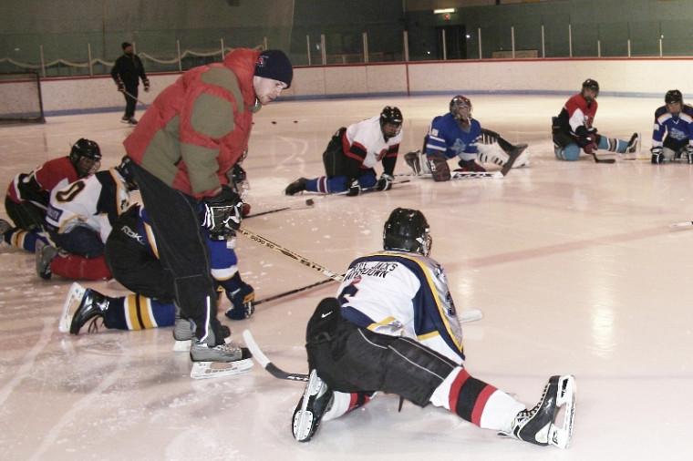 Bruno-Pierre Bernard (debout) œuvre auprès de jeunes hockeyeurs du Nunavik tout en veillant à leur persévérance scolaire.