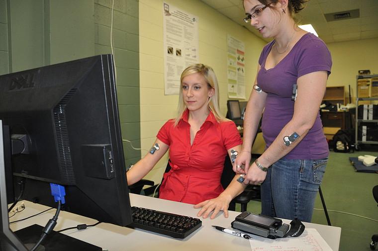 À l'aide d'électrodes, les stagiaires mesurent l'activité musculaire en cours lors du travail à un poste informatique.