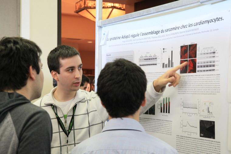 Un étudiant présente son affiche scientifique