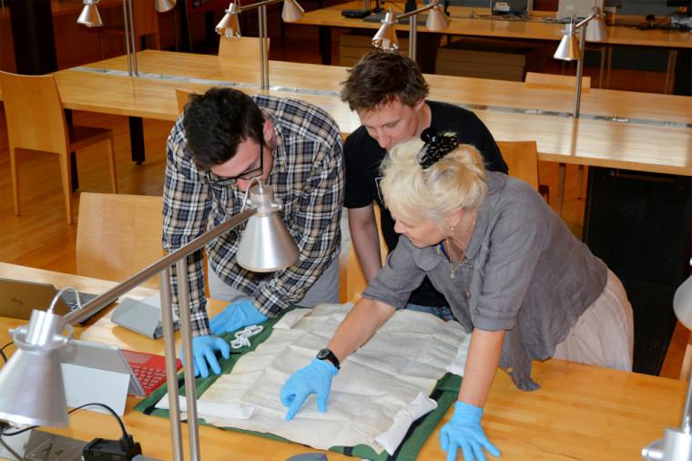 La professeure Geneviève Dumas et deux de ses étudiants en histoire travaillant sur un document ancien.