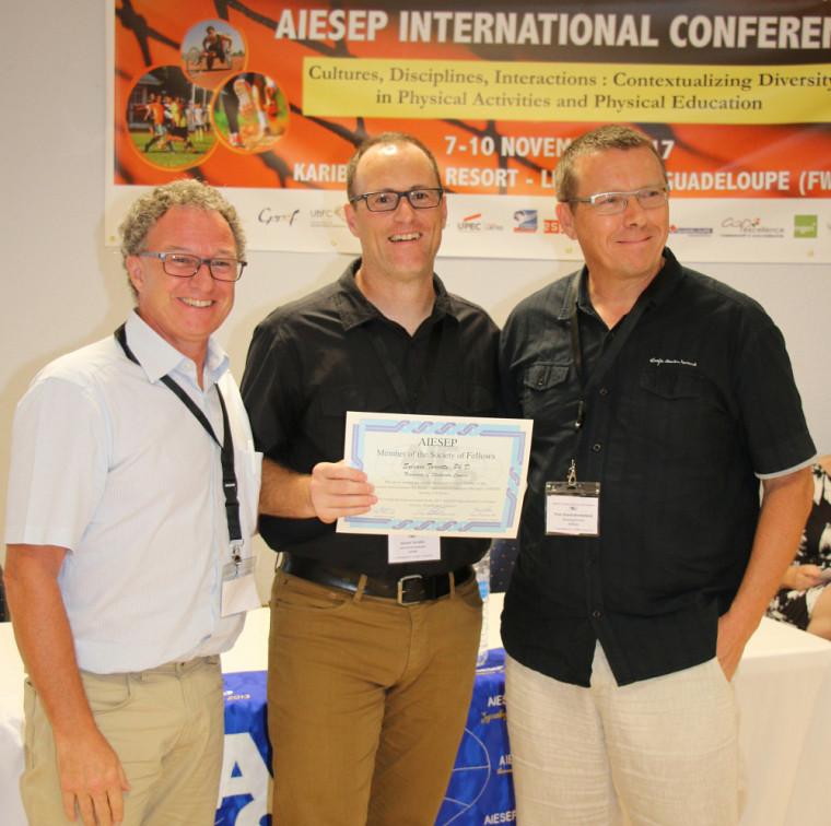 Le professeur Sylvain Turcotte a reçu le titre de Fellow de l'AIESEP. On le voit en compagnie du professeur Marc Cloes, président de l'AIESEP, et du professeur Hans Peter Brandl-Bredenbeck, responsable du Fellowship Award.