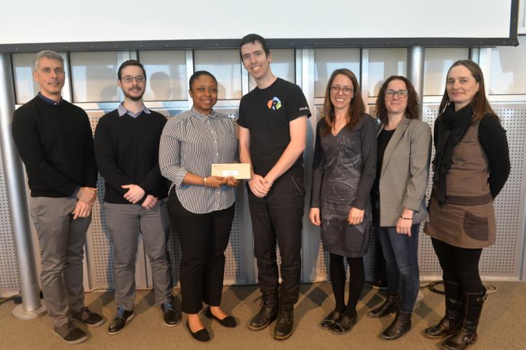 La gagnante s'est vu remettre un prix en argent de 250 $ du Regroupement des étudiantes et des étudiants de maîtrise, de diplôme et de doctorat de l'Université de Sherbrooke (REMDUS). La voici en présence d'un représentant du REMDUS et des membres du jury.