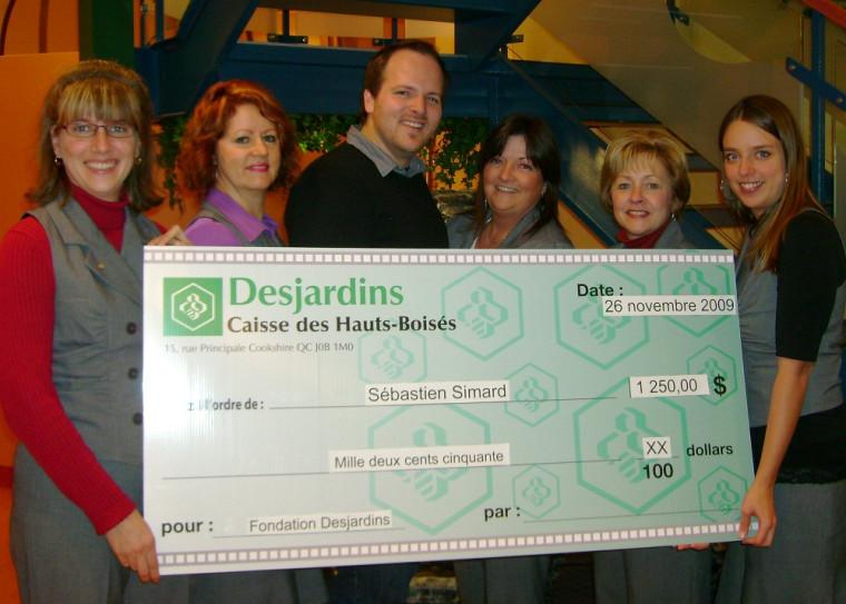 Sébastien Simard, au centre, entouré de membres du personnel de la Caisse Desjardins des Hauts-Boisés de Cookshire.