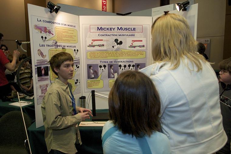 Édouard Caron-Duval à l'Expo-sciences Bell 2009, explique à des visiteurs son projet devant l'objectif de son père.