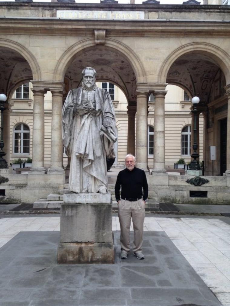 Le Pr André-Marie Tremblay dans la cour du Collège de France, à côté de la statue de Guillaume Budé, sous les conseils duquel François premier a fondé l'institution.