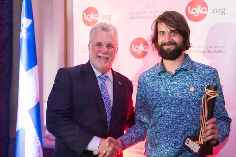 Renaud Lafortune reçoit leGrand Prix LOJIQ des mains du premier ministre du Québec, Philippe Couillard, lors de la8e cérémonie des Prix LOJIQqui s'est tenue le 31 mai à l'Assemblée nationale du Québec.