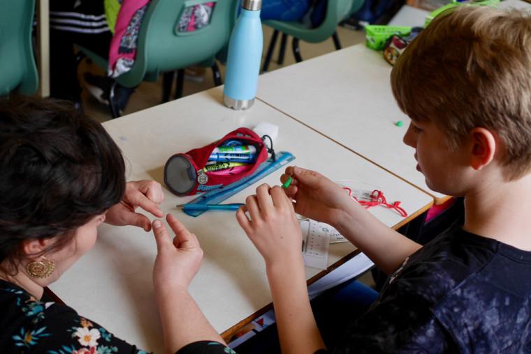 Une enseignante aide un élève d'une école montréalaise à confectionner une chenille-appât qui servira à réaliser une expérience de biologie en contexte réel.