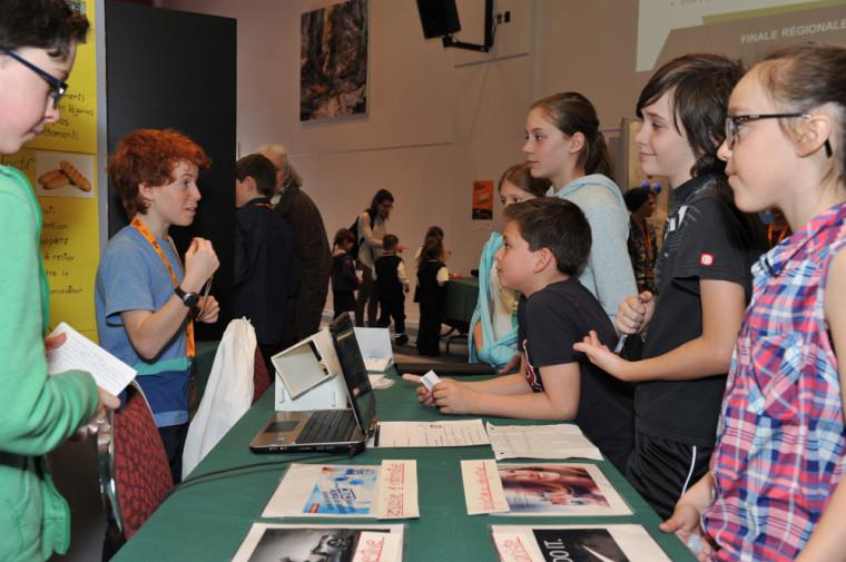 De jeunes visiteurs écoutent Elliot Christin et Jasmin Ricard présenter leur projet «Quel est l'effet des pubs». Kiosque 53, École des Enfants-de-la-Terre.