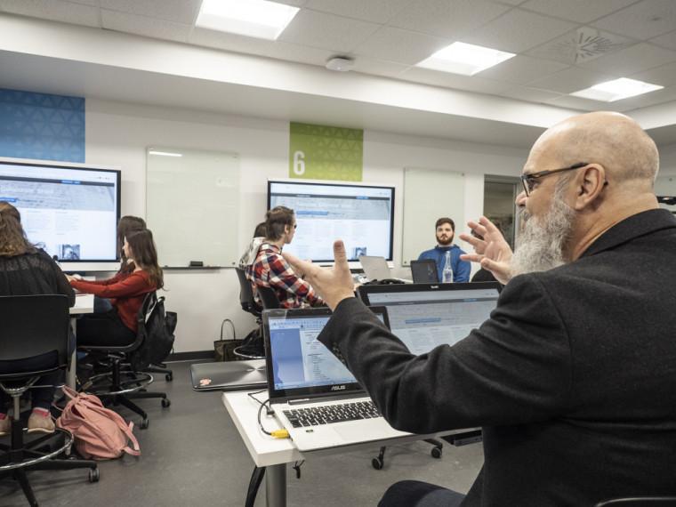 Dans cette salle d'apprentissage actif, le professeur se trouve au centre de la classe, et les équipes d'étudiantes et étudiants sont autour de lui.