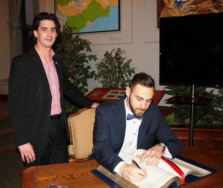 Le conseiller municipal Vincent Boutin et le quart-arrière du Vert & Or Jérémi Roch, signant le livre d'honneur de la Ville de Sherbrooke, le 25 novembre dernier.