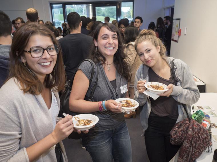 Des étudiantes venues de l'international savourent une traditionnelle poutine lors de la soirée de bienvenue.
