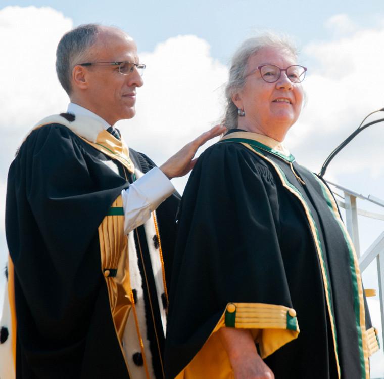 Le recteur de l'UdeS, le professeur Pierre Cossette, investit des couleurs du Vert et Or la docteure d'honneur de la Faculté de génie, l'ingénieure et professeure-chercheure Mme Claire Deschênes.
