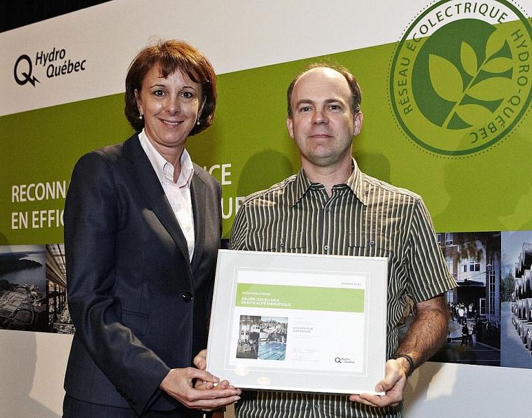 Claude Handfield, directeur de la section Ingénierie au Service des immeubles, reçoit la certification d'Isabelle Courville, d'Hydro-Québec.