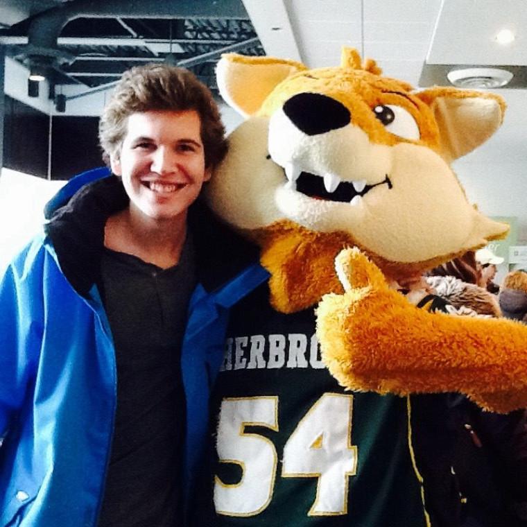 Un visiteur se fait prendre en photo avec Sherlo, la mascotte officielle du Vert et Or!