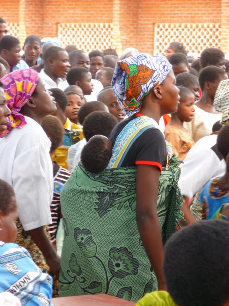 Une dame à l'église avec son enfant sur le dos.
