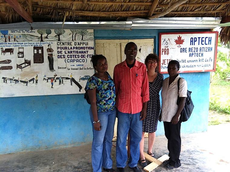 Deux étudiantes de l'Université publique du Sud-Est à Jacmel, Nadine Saint-Germain et Louisena Gontrand, et le directeur de l'École professionnelle de Jacmel, Christian Duplan, dans l'un des ateliers du réseau coopératif APTECH à LaBiche.