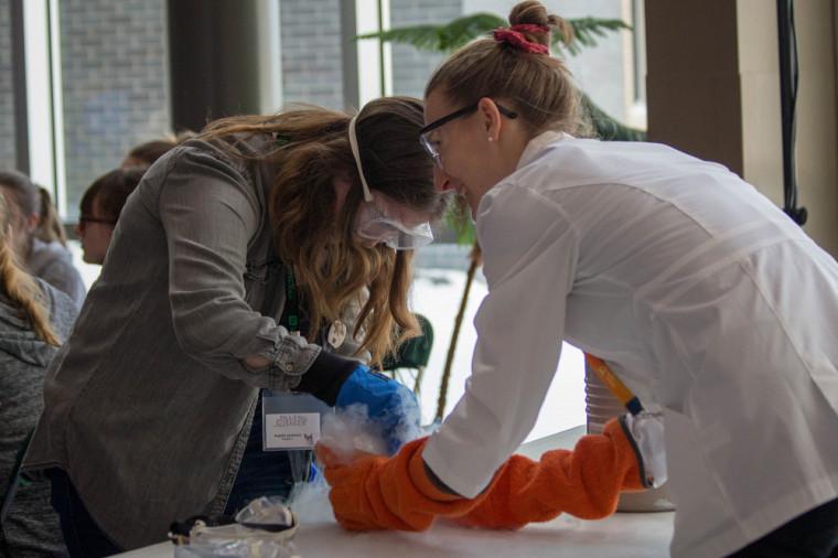 Une participante prépare sa crème glacée à L'azote liquide avec l'aide d'Apolline Benoist.