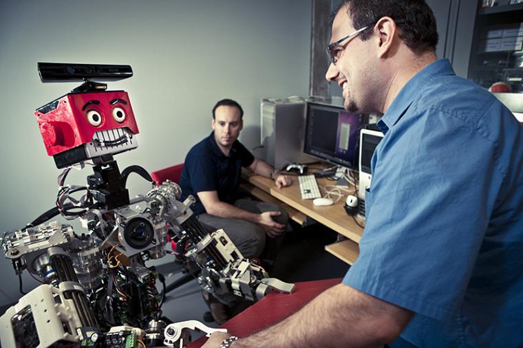 Le professeur Waël Suleiman du Département de génie électrique et de génie informatique interagissant avec un robot.