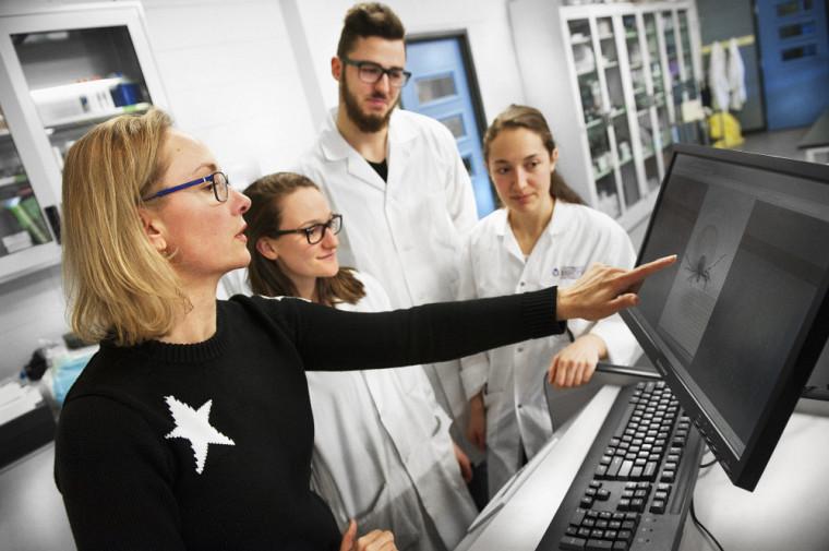 La Pre Savage dans son laboratoire de recherche avec des étudiantes et étudiants.
