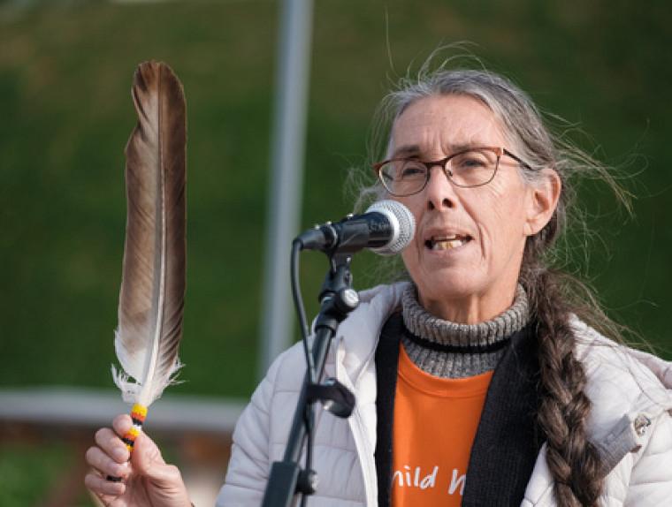 L'Aînée Nicole O'Bomsawin a prononcé une prière appelant à la paix et à l'harmonie entre les peuples, en tenant une plume symbolisant notre désir commun de chasser ce qui nous éloigne les uns des autres.