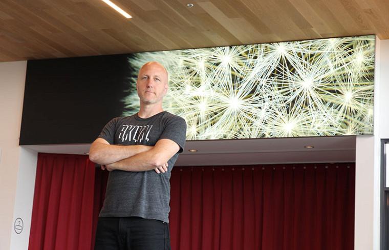 L'artiste et chargé de cours Sébastien Pesot devant l'oeuvre Mal floral.