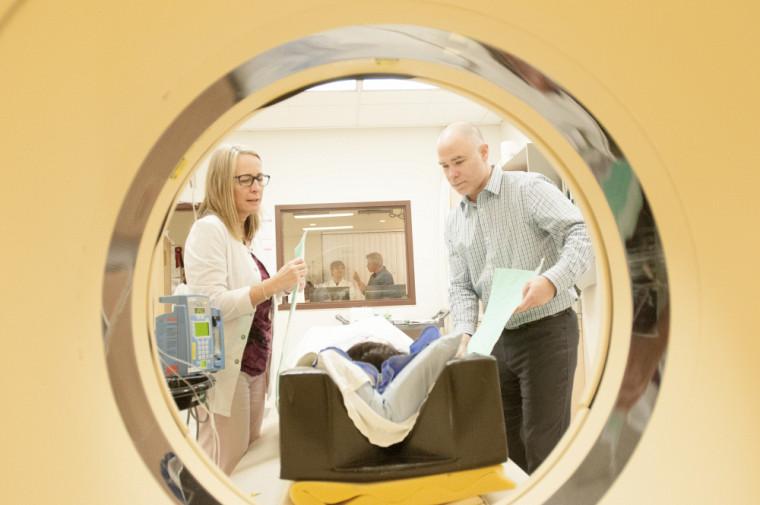 Denis Blondin, stagiaire postdoctoral, est en train de préparer le patient. Le Pr André Carpentier (derrière la fenêtre) est en discussion avec les membres de son équipe de recherche.