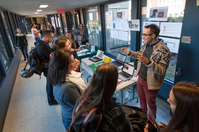 Le professeur Matthieu Petit, du Département de pédagogie, discutant de l'outil d'annotation vidéo en ligne VideoAnt avec des visiteuses.