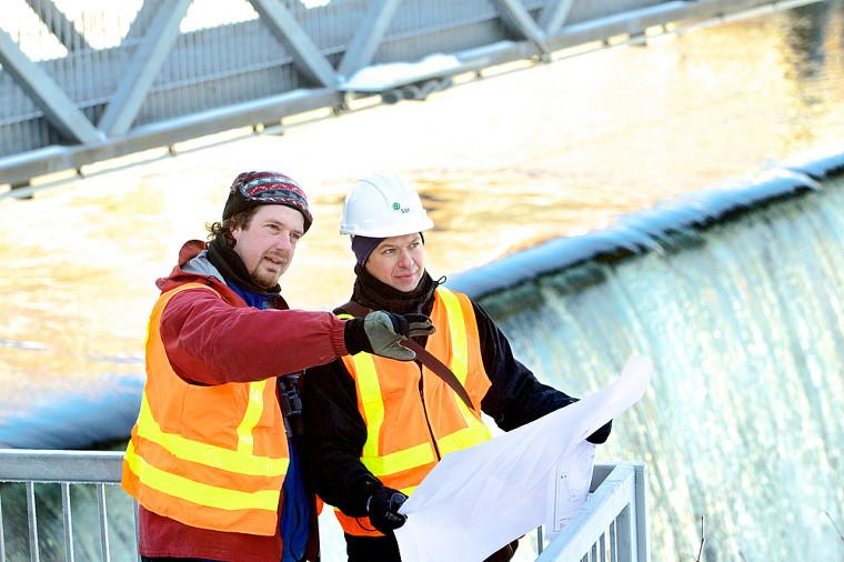 Éric, écologiste, et Anderson, ingénieur, discutent de mesures d'atténuation environnementales pour la réfection d'un barrage.