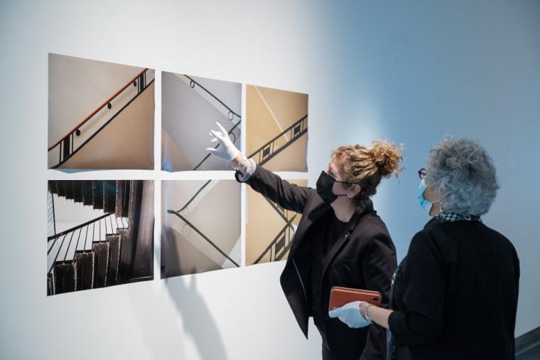 Les professeures Jocelyne Faucher, secrétaire générale et vice-rectrice à la vie étudiante, et Anick Lessard, doyenne de la FLSH, devant une œuvre photographique de l'exposition.