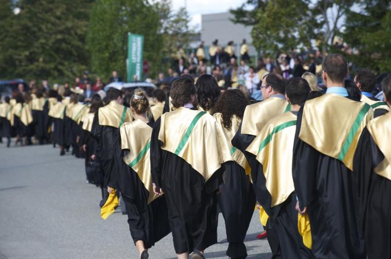 Des diplômés couverts d'or et de vert.