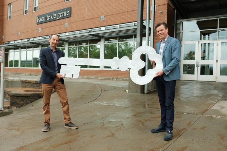 Le professeur Patrik Doucet, à droite, qui passe une symbolique clé de 2 mètres à son successeur, le professeur Jean Proulx!