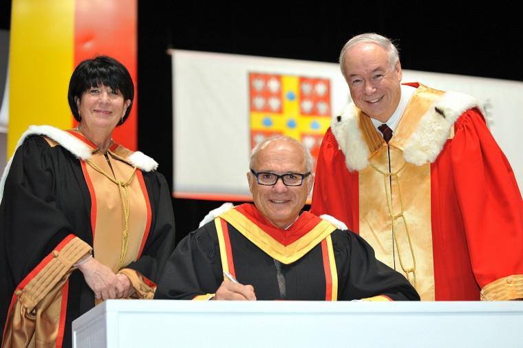 Le professeur Grand'Maison signe un registre, entouré de la secrétaire générale Monique Richer et du recteur Denis Brière de l'Université Laval.